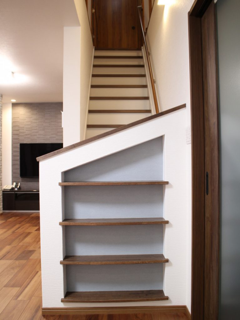【階段】 勾配も緩やかになり安心して昇り降りできるようになりました。 U様のご希望で手摺下部には飾り棚を設けました。